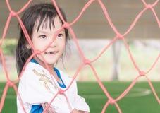 A menina da criança do futebol está estando dentro de um objetivo do futebol no campo de treinamento do futebol fotos de stock