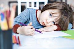 Menina da criança do retrato que guarda o lápis da cor que senta-se apenas e que olha para fora com cara furada fotografia de stock