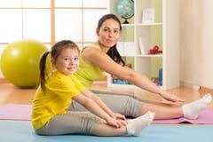 A menina da criança e sua mãe que fazem o gym exercitam em casa foto de stock royalty free