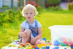 Menina da criança em idade pré-escolar que joga com blocos do plástico fora foto de stock royalty free