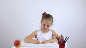 A menina da criança em idade pré-escolar senta-se em uma mesa e tira-se diligently um desenho video estoque