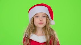 A menina da criança em tampões vermelhos do Natal envia beijos do ar Tela verde video estoque