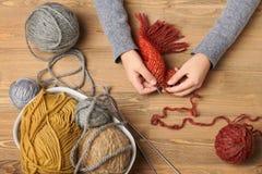 A menina da criança está aprendendo fazer malha Os fios de lãs coloridos estão na tabela de madeira Close up da mão foto de stock