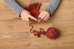 A menina da criança está aprendendo fazer malha um lenço O fio de lãs vermelho está na tabela de madeira Close up da mão fotografia de stock