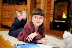 A menina da criança está lendo na frente da chaminé Foto de Stock