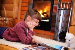 A menina da criança está lendo na frente da chaminé Foto de Stock Royalty Free