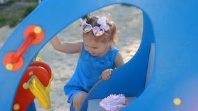 A menina da criança está montando um helicóptero do carrossel em um parque de diversões Jogos do bebê no campo de jogos filme