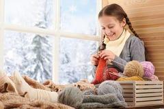 A menina da criança está sentando-se em um peitoril da janela com fios e confecção de malhas de lãs Vista bonita fora da janela - imagens de stock royalty free