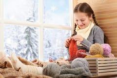 A menina da criança está sentando-se em um peitoril da janela com fios e confecção de malhas de lãs Vista bonita fora da janela - imagem de stock royalty free