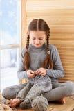 A menina da criança está sentando-se em um peitoril da janela e está fazendo-se malha o lenço do fio de lãs cinzento Vista bonita imagens de stock royalty free