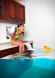 A menina da criança faz a confusão, cozinha inundada imitando a piscina, f imagens de stock