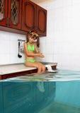 A menina da criança faz a confusão, cozinha inundada imitando a piscina, f fotos de stock royalty free