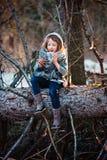 A menina da criança joga com os cones do pinho na floresta do inverno do início de uma sessão da árvore Imagens de Stock