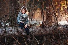 A menina da criança joga com os cones do pinho na floresta do inverno do início de uma sessão da árvore Foto de Stock Royalty Free