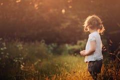Menina da criança na camisa branca na caminhada no campo do por do sol do verão Imagens de Stock