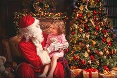 Menina da criança na camiseta que senta-se no regaço de Santa Claus em torno de Chr fotografia de stock