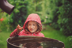 Menina da criança na capa de chuva vermelha que joga com o tambor da água no jardim chuvoso do verão Economia da água e cuidado d fotografia de stock