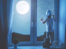 Menina da criança na janela que sonha o céu estrelado em horas de dormir fotos de stock