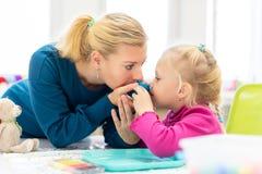 Menina da criança na sessão de terapia ocupacional da criança que faz exercícios brincalhão sensoriais com seu terapeuta imagens de stock royalty free