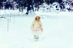 Menina da criança no casaco de pele que anda em um parque nevado do inverno Fotos de Stock Royalty Free