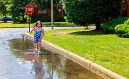 Menina da criança no salto nas poças após a chuva do verão imagens de stock