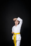 Menina da criança no terno do karaté com posição amarela da mostra da correia Fotos de Stock Royalty Free
