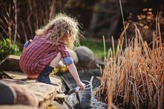 Menina da criança no vestido da manta que recolhe a água da lagoa no jardim da mola Fotografia de Stock