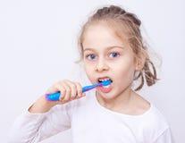 Menina da criança nos pyjamas que escovam os dentes - higiene das horas de dormir Fotografia de Stock