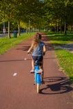 A menina da criança ou do adolescente aprecia o bom tempo e o ciclismo fotos de stock