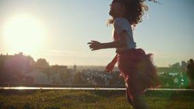 A menina da criança pequena é de corrida, de jogo e de riso, lento-movimento filme