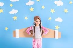 A menina da criança pequena em um traje do astronauta é de jogo e de sonho de transformar-se um astronauta Foto de Stock