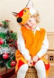 A menina da criança pequena vestiu-se no terno da raposa perto da árvore de Natal Foto de Stock Royalty Free