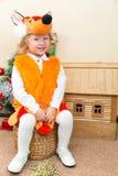A menina da criança pequena vestiu-se no terno da raposa perto da árvore de Natal Imagem de Stock Royalty Free