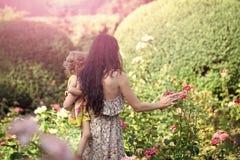 Menina da criança da posse da mulher em rosas de florescência no dia idílico Imagens de Stock