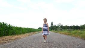 Menina da criança que anda ao longo de uma estrada rural filme