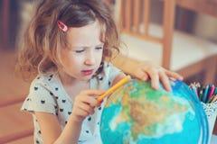 Menina da criança que aprende com globo em casa Fotos de Stock Royalty Free