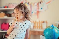Menina da criança que aprende com globo em casa Imagens de Stock Royalty Free