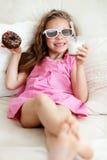 Menina da criança que come em um sofá Imagem de Stock