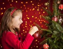 Menina da criança que decora a árvore de Natal na obscuridade - vermelho com luzes Imagens de Stock Royalty Free