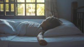 Menina da criança que dorme na cama em casa e que acorda lentamente na manhã vídeos de arquivo