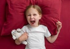 A menina da criança que encontra-se na cama recusa dormir imagens de stock