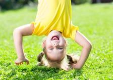 Menina da criança que está de cabeça para baixo em sua cabeça sobre Foto de Stock Royalty Free