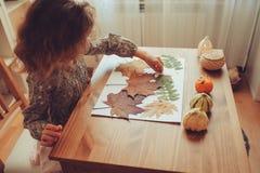 Menina da criança que faz o herbário das folhas secadas em casa, da arte da natureza e do ofício imagem de stock royalty free