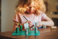 Menina da criança que faz o jogo do dedo do pé do tac do tique do ofício de easter em casa Imagens de Stock Royalty Free
