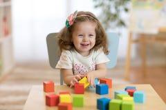 Menina da criança que joga brinquedos de madeira em casa ou jardim de infância Imagem de Stock