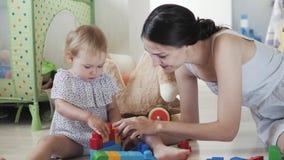 Menina da criança que joga brinquedos de madeira em casa ou jardim de infância, desinger intelectual do ` s das crianças dos jogo filme