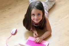 Menina da criança que joga com brinquedo do portátil Fotografia de Stock Royalty Free