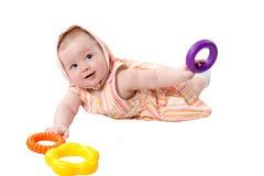 Menina da criança que joga com construção da pirâmide do brinquedo dos anéis isolados Fotos de Stock