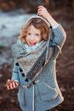 Menina da criança que joga com os cones do pinho na caminhada na floresta do inverno Imagens de Stock