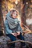 Menina da criança que joga com os cones do pinho na caminhada na floresta do inverno, sentando-se na árvore velha Fotos de Stock